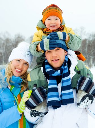 outsides: happy young family spending time outdoor in winter park