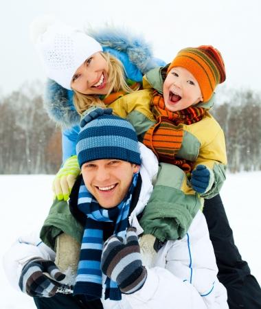 ropa de invierno: familia feliz, la joven pareja y su hijo pasar tiempo al aire libre en invierno