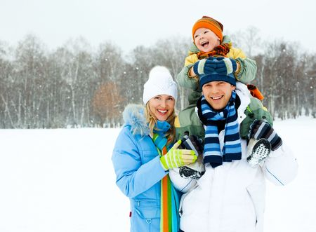 having fun in the snow: happy young family spending time outdoor in winter park