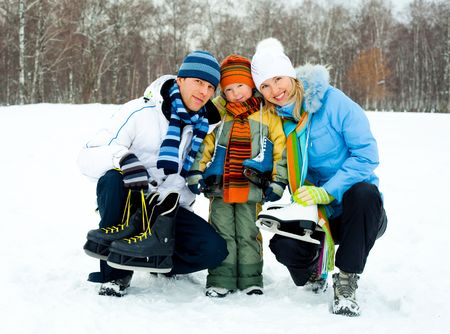 skating rink: happy young parents going ice skating with their son