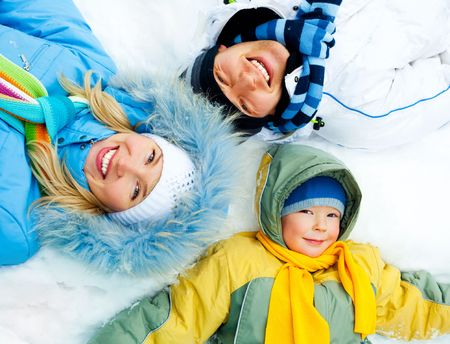 young parents and their son wearing warm winter clothes lie on the snow photo