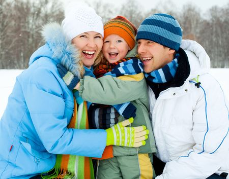 winter woman: happy young family spending time outdoor in winter