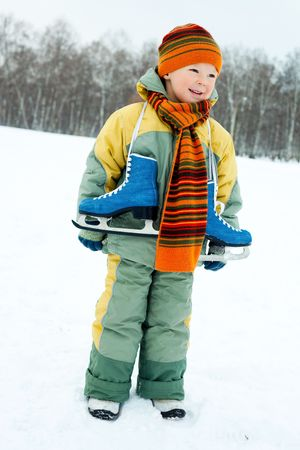 cute little boy wearing warm winter clothes going ice skating  photo