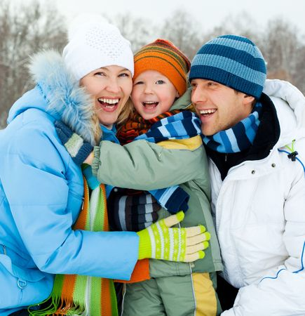 outsides: happy young family spending time outdoor in winter