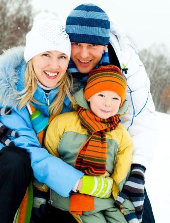 冬の屋外の時間を過ごす幸せな若い家族