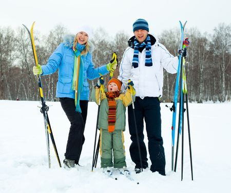 winter day: happy young couple going skiing with their son on a warm winter day