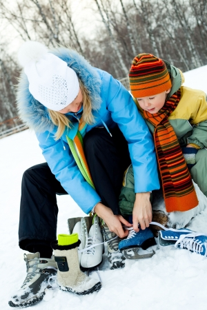 iceskating: happy young mother and her son tightening laces and getting ready to go ice-skating