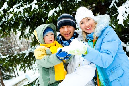pine three: happy young mother, father and their little son spending time outdoor in winter park Stock Photo