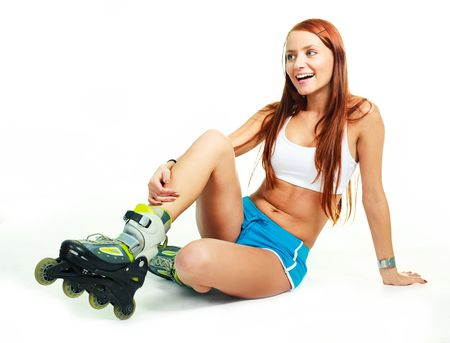 rollerskates: pretty happy girl with rollerskates sitting on the floor