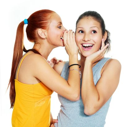 Retrato de dos hermosas niñas gossiping sobre fondo blanco
