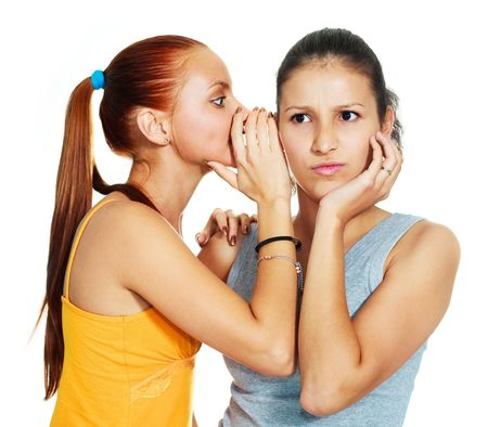 complications: portrait of two beautiful gossiping girls against white background Stock Photo