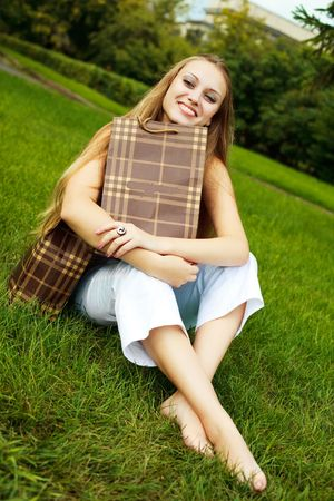 happy young blond woman sitting on the grass with shopping bags Stock Photo - 6027577