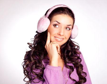 earmuff: pretty thoughtful brunette woman wearing pink earmuff Stock Photo