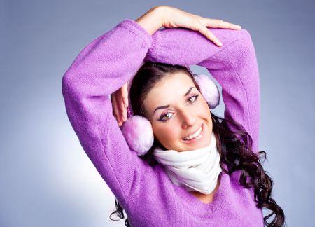 earmuff: pretty young happy brunette woman wearing pink earmuff Stock Photo