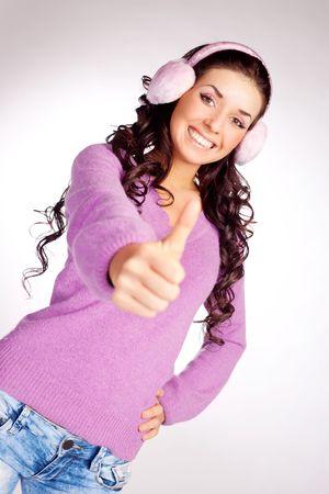 earmuff: happy brunette girl wearing earmuff with her thumb up Stock Photo