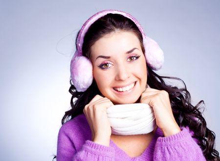 earmuff: pretty young happy brunette woman wearing pink earmuff and a scarf