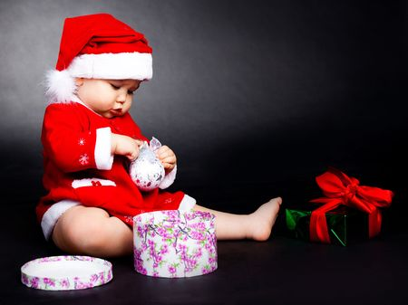 get dressed: happy baby dressed as Santa opening the christmas presents Stock Photo