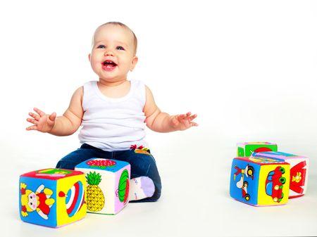 jouet: cute b�b� heureux assis sur le sol et de jouer avec les jouets