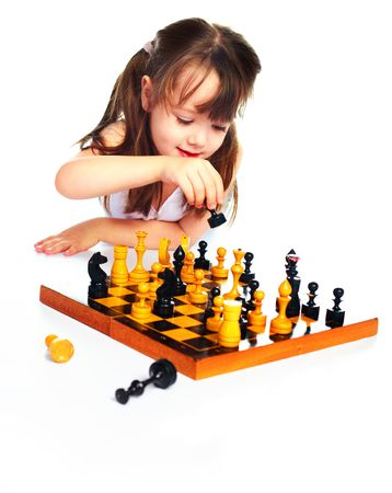 cute thoughtful girl playing chess on the floor photo