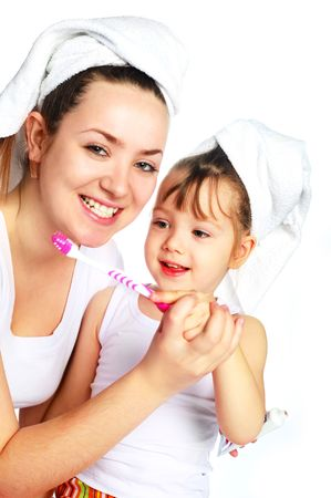young beautiful mother and her little daughter brushing teeth and laughing Stock Photo