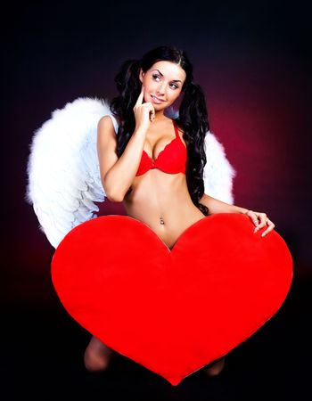 sexy young woman with a big heart in her hands photo