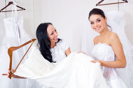 pretty young woman is choosing a wedding dress in the shop and the shop assistant is helping her photo