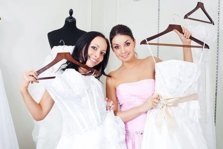 pretty young women  choosing  wedding dresses in the shop  photo