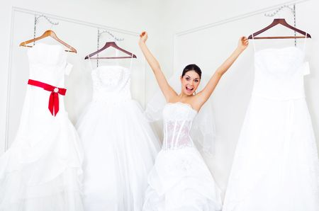 make a choice: pretty young excited woman is choosing a wedding dress in the shop