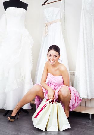 girl in dress: pretty young woman is choosing a wedding dress in the shop   Stock Photo