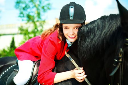 horse laugh: pretty young woman riding a black horse