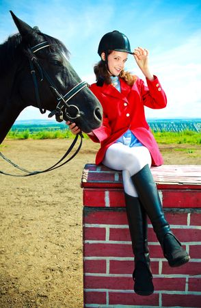 portrait of a pretty young woman with a black horse photo