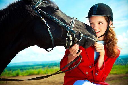 caballo jinete: Retrato de una mujer muy joven con un caballo negro