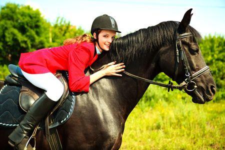 portret van een mooie jonge vrouw die een zwart paard  Stockfoto