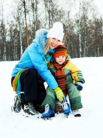 young beautiful mother teaching her little son ice skating photo
