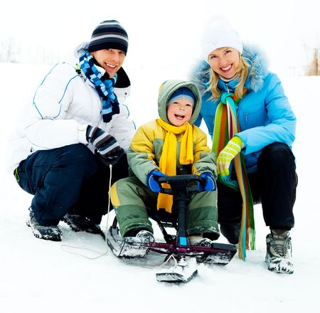 young father and mother and their little sun on the sledge photo