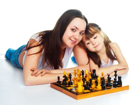 young mother and her daughter playing chess together photo