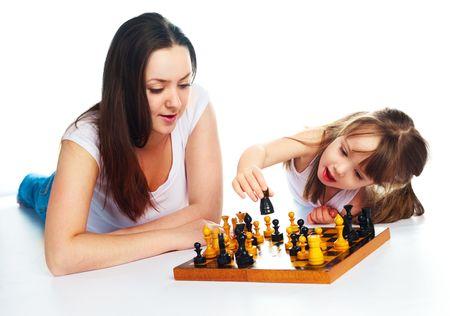 jugando ajedrez: joven madre y su hija jugando al ajedrez juntos Foto de archivo
