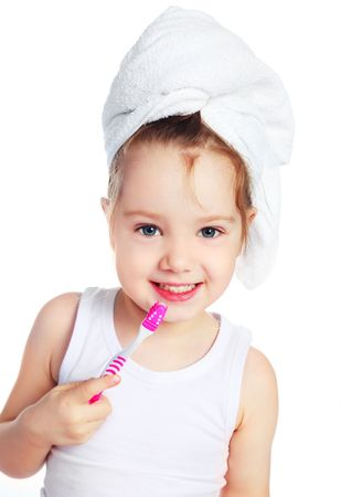 tooth care: cute little girl with a towel on her head brushing her teeth