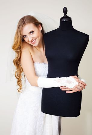 beautiful young woman wearing a wedding dress with a dummy in the shop photo