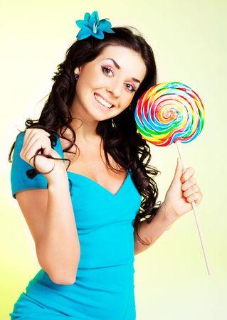 paletas de caramelo: bastante sonriente chica Morena con una paleta en la mano