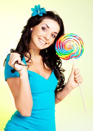 pretty smiling brunette girl with a lollipop in her hand Stock Photo - 6601868