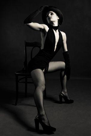 donna seduta sedia: jazz ballerino indossa un cappello a cilindro nero, una farfalla farfallino e guanti, danza con una sedia Archivio Fotografico