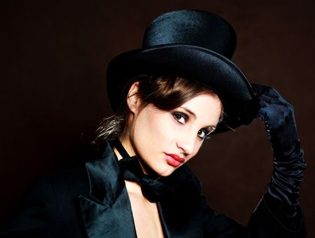 female sexuality: beautiful young brunette woman wearing a black cylinder hat, a smoking jacket and a butterfly bow tie  Stock Photo