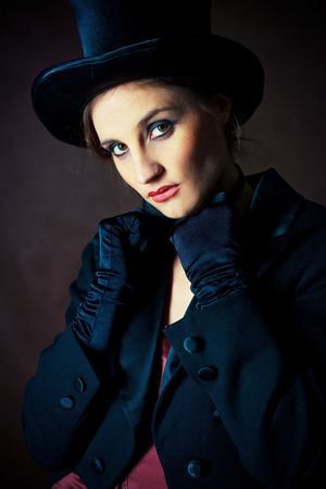 beautiful young brunette woman wearing a black cylinder hat, a smoking jacket and a butterfly bow tie  photo