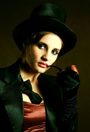 beautiful young brunette woman wearing a black cylinder hat, a smoking jacket and a butterfly bow tie smoking a pipe photo