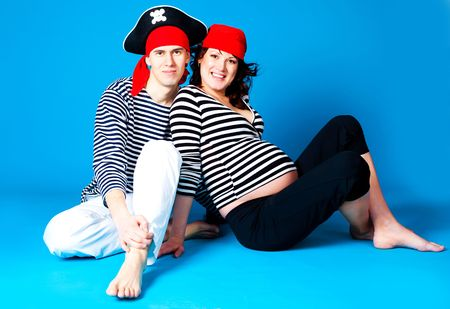 young happy pregnant woman and her husband dressed as pirates photo