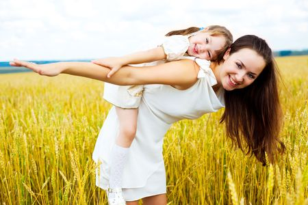 beautiful young mother and her daughter at the wheat field on a sunny day (focus on the child) photo