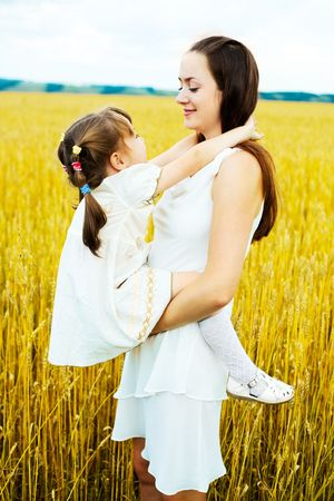 beautiful young mother and her daughter at the wheat field on a sunny day photo