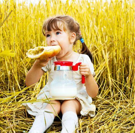 niedliche kleine Mädchen im Weizenfeld, Essen eine lange Loaf und trinken Milch