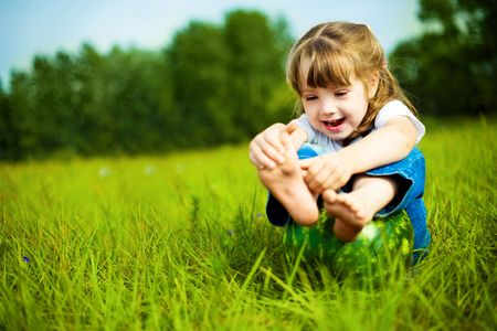 cute little girl with a water-melon on the grass in summertime photo
